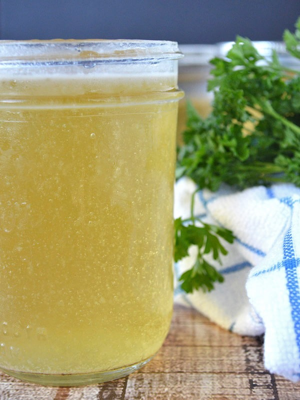 An open mason jar holding slow cooker chicken stock that is not only incredibly easy to make, but it's so much more flavorful than any chicken stock I've bought at the store. Which is to the left of a blue and white towel and a bundle of parsley.