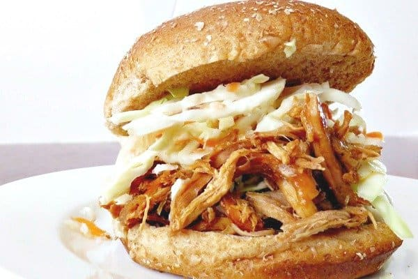Pulled pork sandwich with coleslaw in a whole wheat bun on a plate.
