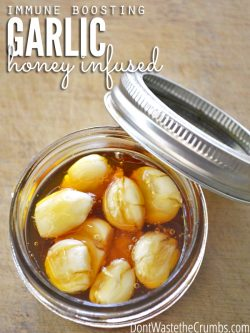 "Jar of honey infused garlic cloves with text overlay, ""Immune Boosting Garlic Honey Infused""."