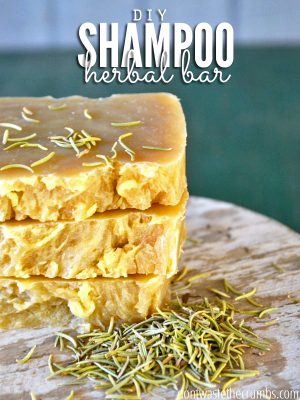 """Three shampoo bars stacked up on a counter with herbs sprinkled around. Text overlay says, """"DIY Shampoo Herbal Bar""""."""