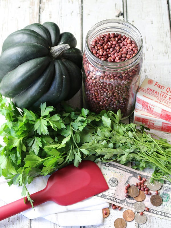 An acorn squash sits beside a jar of dried beans with a bunch of cilantro and 2 sticks of butter. This illustrates how cooking from scratch is an easy way to save money.