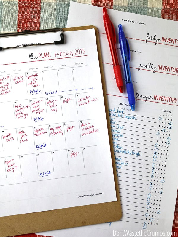 A paper calendar with meals written on in, and freezer, pantry and fridge inventory papers behind it, with two pens on top ready for planning Freezer Cooking Day.