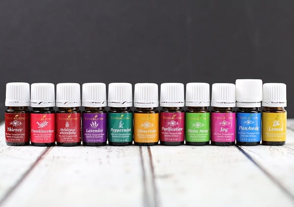 A line up of colorful Young Living Essential oil bottles sitting next to each other on table with a dark background. Some oils include Thieves, Lavender, Peppermint, Stress Away, and lemon.