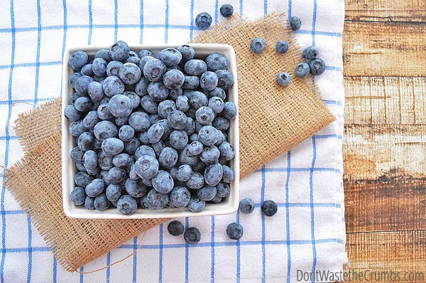 Basket full of blueberries on a table with a napkin and more blueberries.