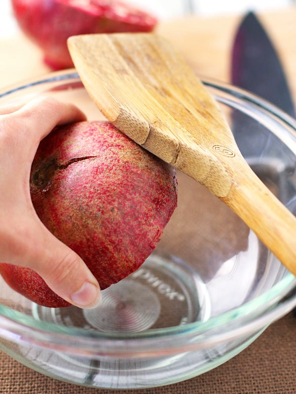 Hit the pomegranate with a wooden spoon to release all of the arils or seeds.