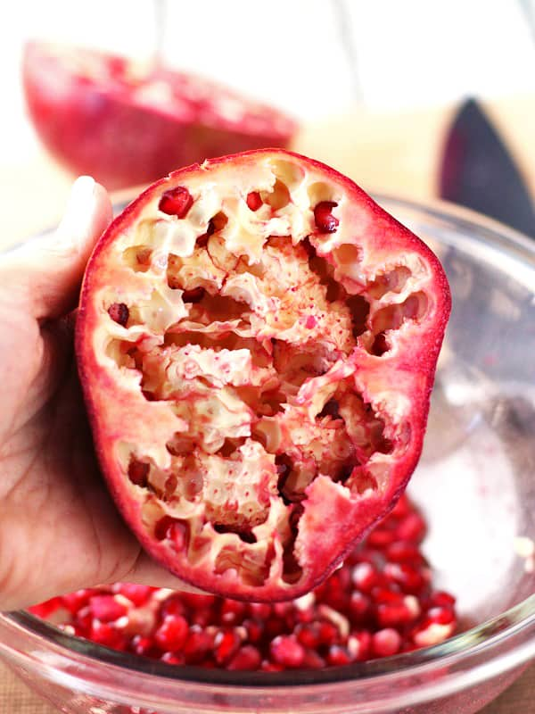 The seeds of the pomegranate will loosen up and become easier to remove as you hit the half of the pomegranate with a wooden spoon!