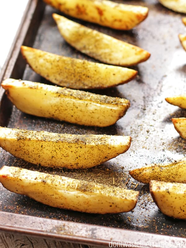 Baked potato fries sprinkled with seasonings on a baking sheet.