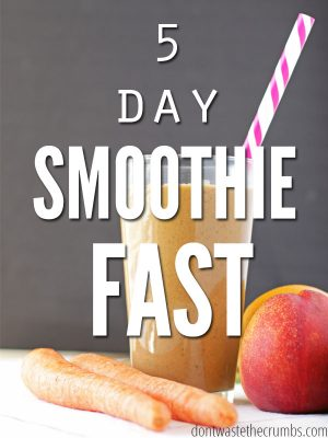 Glass filled with carrot smoothie with a white and purple striped straw. Raw carrots and a nectarine sitting next to the glass on a white table cloth . Text overlay 5 Day Smoothie Fast.