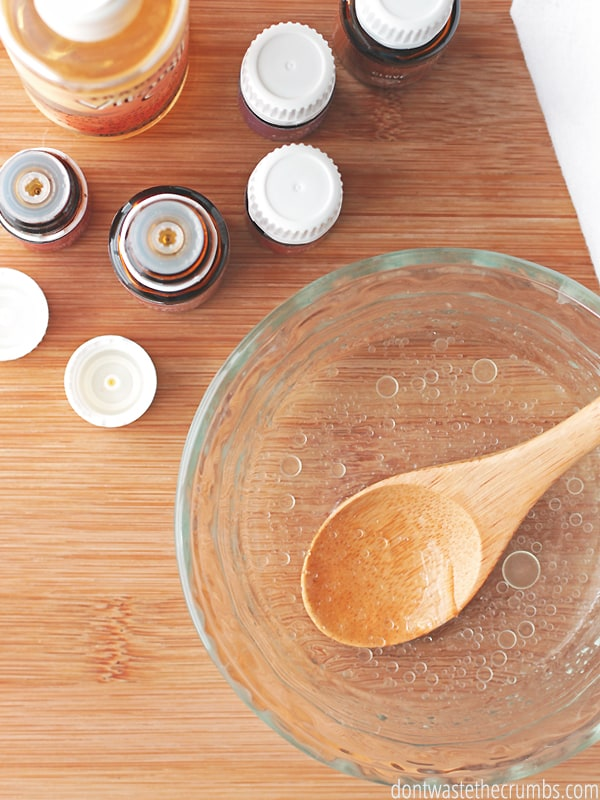 A clear bowl filled with Vitamin E oil, essential oil drops and a wooden spoon inside stirring it. There are five bottles of essentials oils, and vitamin E oil.