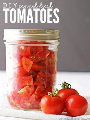 "Mason jar with canned diced tomatoes and a few fresh tomatoes sitting in front of it. Text overlay says, ""DIY Canned Diced Tomatoes""."