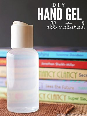 "Bottle of hand sanitizer with a stack of books in the background with text overlay, ""DIY Hand Gel All Natural""."