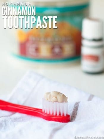 Red Toothbrush with toothpaste. Blurred in the background is tub of Bentonite Clay and a bottle of Cinnamon Bark essential oil. Text overlay Homemade Cinnamon Toothpaste.