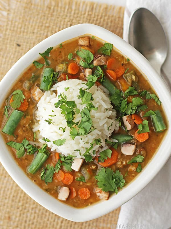 Lentil and vegetable soup topped with a fluffy scoop of white rice.
