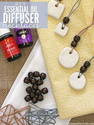 Bottles of Raven and Lavender essential oils, wooden necklace beads, bent paper clips and four completed necklaces. Text overlay DIY Essential Oil Diffuser Necklace