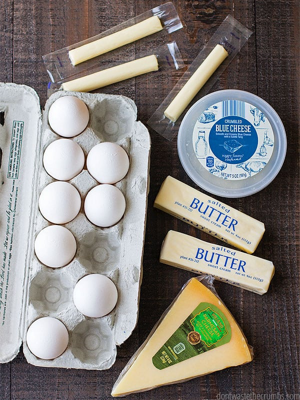 There are eggs, string cheese, butter, blue cheese and parmesan cheese laid out waiting to be cooked into a quick and easy meal that is in our one week $50 ALDI meal plan.