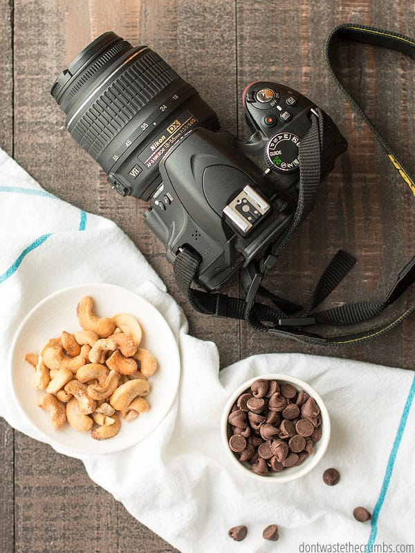 A large Nikon camera with a strap set upon a dark table, next to a plate of cashews and a bowl of chocolate chips. Which are on a white and blue towel.