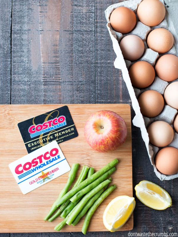 12 packaged eggs on a dark wood table in the upper right corner. The bottom left of the picture has a light wooden cutting board with two Costco cards, a single apple, a pile of green beans, and two lemon slices laid on it.