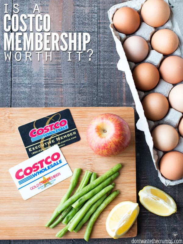 The cover photo of our, Is a Costco membership worth it post. A carton of eggs lay on a dark wood table in the upper right corner. The bottom left of the picture has a light wooden cutting board with two Costco cards, a single apple, a pile of green beans, and two lemon slices laid on top of it.