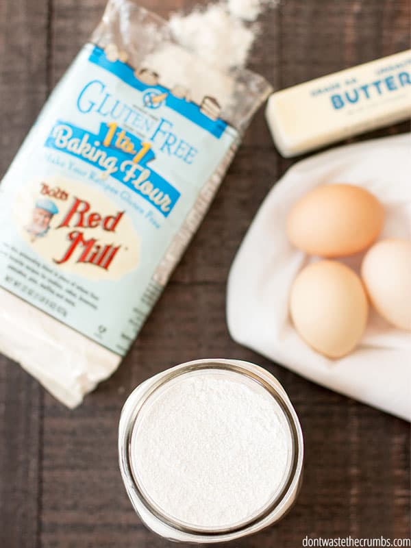 A bag of Bob's Red Mill Gluten Free Baking Flour sits next to a jar of sugar, eggs, and butter.