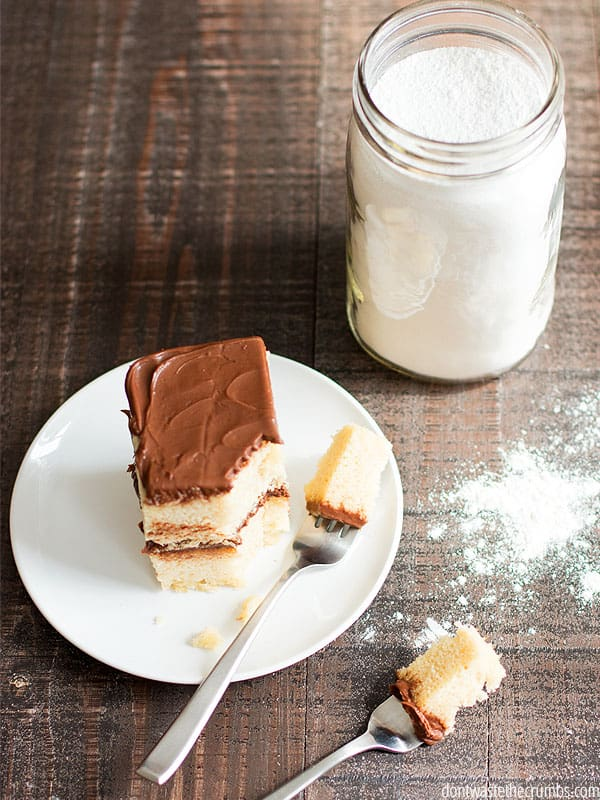 A forkful of cake is sliced from a piece of double layered yellow cake with chocolate frosting. A jar of cake ingredients - flour, sugar, salt, and baking powder - sits next to the plate.