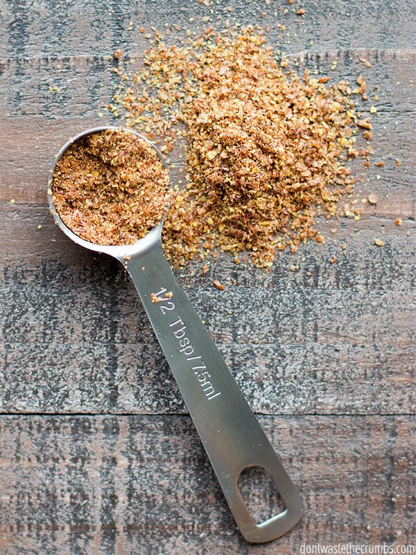 Measuring spoon filled with ground flaxseed and some spilled onto a table.