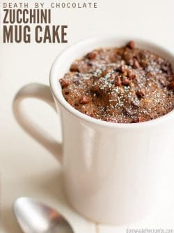 Classic white diner coffee mug filled with chocolate cake. Text overlay Death By Chocolate Zucchini Mug Cake.