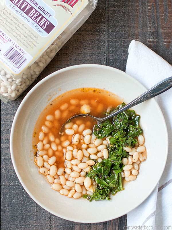Super simple and super frugal, this white bean soup with garlic and kale is the best! It costs less than $5 to make a big batch and freezes great for future meals!