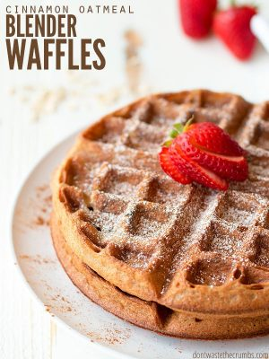 "Two waffles stacked high with strawberries on top and a dusting of powdered sugar with text overlay, ""Cinnamon Oatmeal Blender Waffles""."
