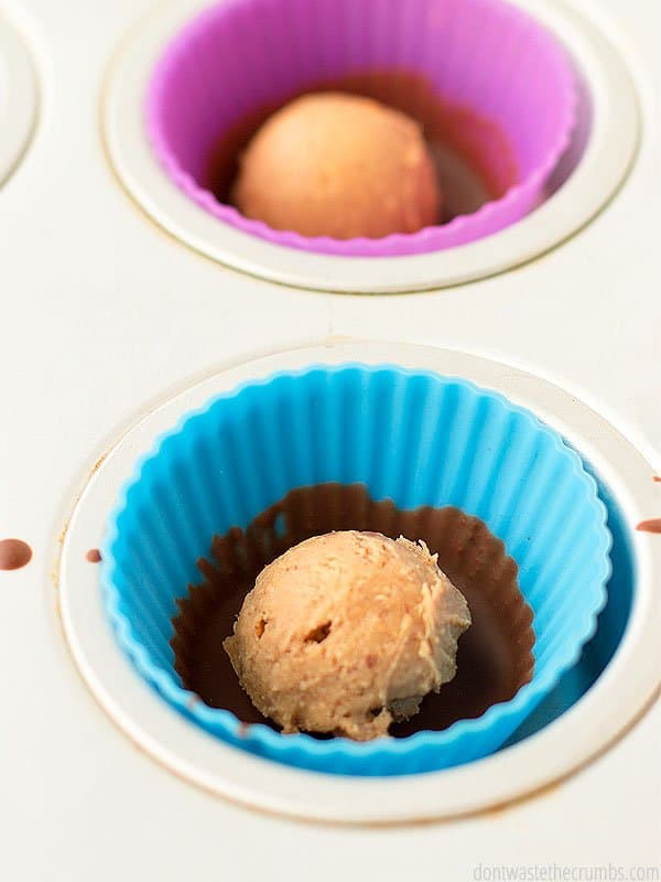 Two scoops of peanut butter, in separate silicone muffin liners that have a light coat of chocolate from the middle down. Set inside a muffin tin.