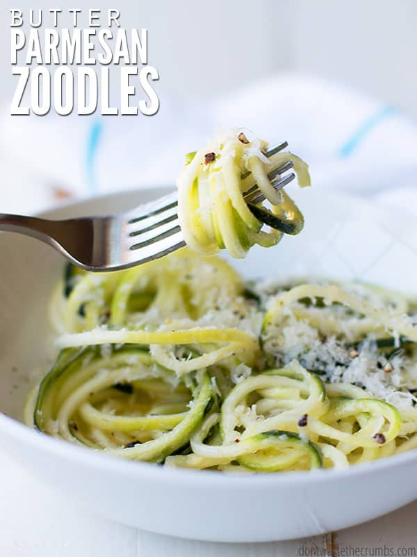 "A bowl of zucchini noodles topped with parmesan cheese and a fork with noodles wrapped around it with text overlay, ""Butter Parmesan Zoodles""."