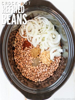"Crockpot filled with dried pinto beans, sliced onion and seasonings with text overlay, ""Crock-Pot Refried Beans""."