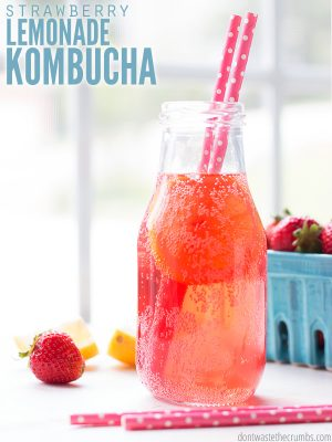 """Bottle of strawberry lemonade kombucha with strawberries in a basket. Text overlay says, """"Strawberry Lemonade Kombucha""""."""