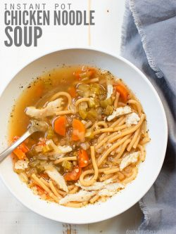 Large round white bowl filled with chicken noodle soup with a spoon clearly showing a recent bite. Text overlay Instant Pot Chicken Noodle Soup.