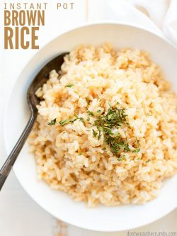 "Bowl of brown rice with parsley on top. Text overlay says, ""Instant Pot Brown Rice""."