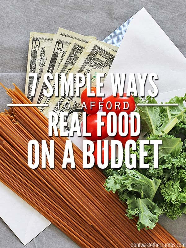 A bunch of uncooked whole grain pasta noodles laid out next to Kale and Cherry Tomatoes, all sitting on a white business envelope with $1 and $5 bills protruding. Text overlay 7 Simple Ways to Afford Real Food on a Budget.