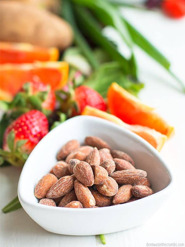 Have you been afraid the Whole30 will break the bank? Use my list of dos and don'ts to find out how you can make the Whole30 affordable! Shown is a bowl of almonds in front of fruits and vegetables.