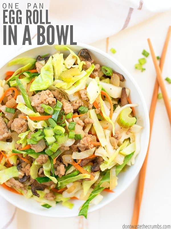 This is the cover to our easy Egg Roll in a Bowl recipe! A white bowl is filled with egg roll mix topped with chives and sitting next to a pair of wooden chop sticks.