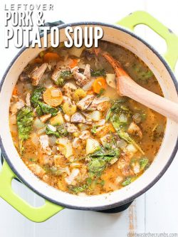 Overview of a large ceramic cooking pot, with green lime green handles and a charcoal colored rim, filled with a hearty soup - chunks of pork, sliced carrots and potatoes, and greens, plus spices all visible. Text overlay Leftover Pork & Potato Soup.