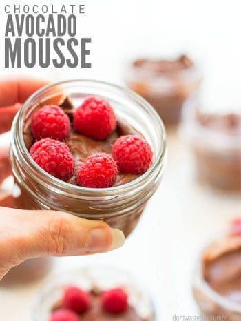 Small glass jar filled with rich chocolate mousse, garnished with ripe raspberries. Text overlay Chocolate Avocado Mousse.