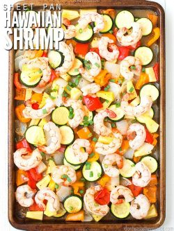 Stone baking sheet filled with peeled shrimp, browned red and orange peppers, white and green onions and pineapple chunks. Text overlay Sweet Pan Hawaiian Shrimp.