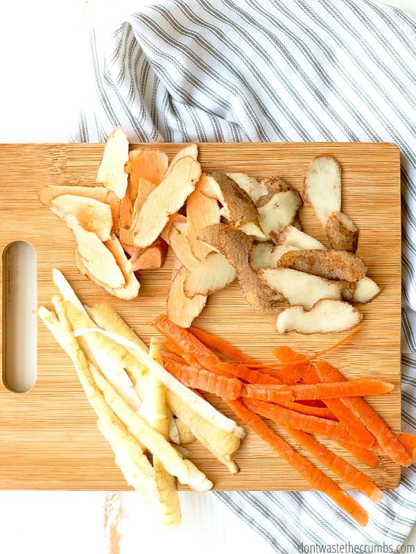 Various carrots, celery, garlic and sweet potato scraps sitting on a whitewashed wooden kitchen table. Text overlay The Best Kitchen Scraps for Stock.