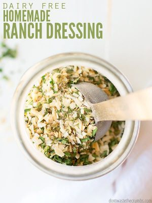Overview, close up look into a Mason jar filled with minced parsley, salt, dried dill and other spices. Small scoop spoon sits in the jar.Text overlay Dairy Free Ranch Dressing.