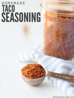 ½ Teaspoon measuring spoon with a heaping scoop of red and orange taco seasoning. Mason jar full of same colorful seasoning in the background. Text overlay Homemade Taco Seasoning.
