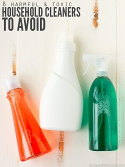 Three plastic dispenser bottles, one clear with red liquid, one clear with green liquid and one a solid white. All on a distressed wood table. Text overlay 8 Harmful & Toxic Household Cleaners to Avoid.