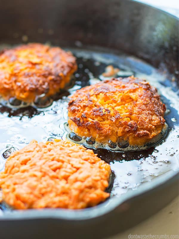 White dinner plate with four round, fried Sweet Potato fritters, one with a bit take out of it. A small dish of dipping sauce sits on the side. Text overlay Carrot Sweet Potato Fritters.