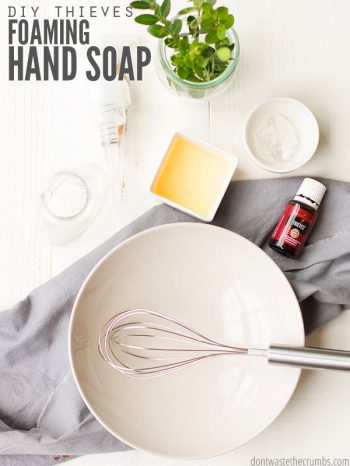 A whisk sitting in a large white bowl, a square bowl filled with Castile Soap, a small bottle of Thieves essential oil and a small bowl filled with Aloe Vera gel, all on a distressed wooden table. Text overlay DIY Thieves Foaming Hand Soup.