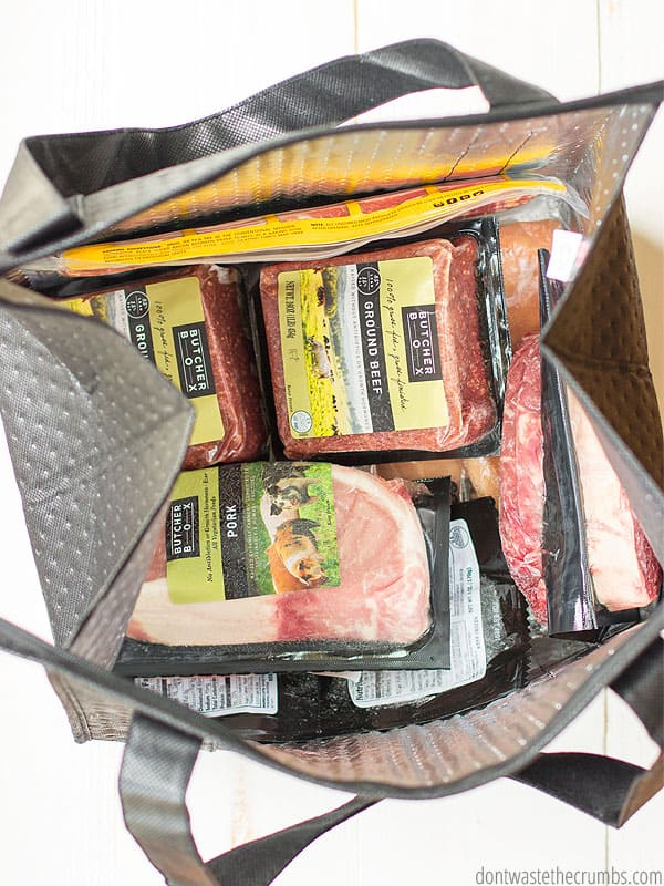 Various packages of frozen meats and chicken, all in Butcher Box packaging, in an insulated tote.