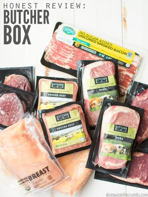 Various packages of frozen meats and chicken, all in Butcher Box packaging, on a whitewashed wooden table top. Text overlay Honest Review: Butcher Box.
