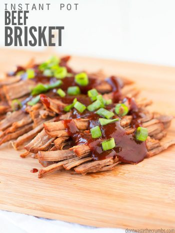 Wooden serving plank with shredded beef brisket, coated with BBQ sauces and diced green onions..Text overlay Instant Pot Beef Brisket.