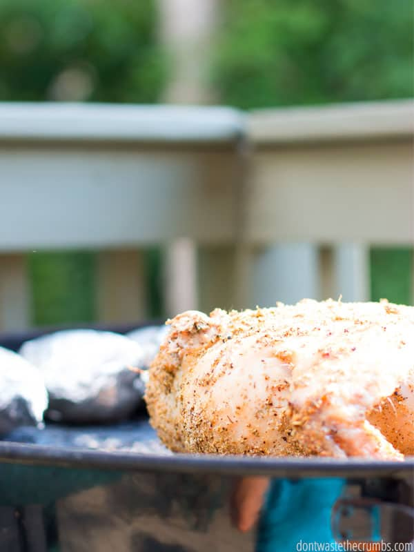 Whole seasoned chicken on round a BBQ grill with a silver set of tongs. Steam rises in the background with two potatoes wrapped in aluminum foil in the foreground. Text overlay One Week Grilling Meal Plan.
